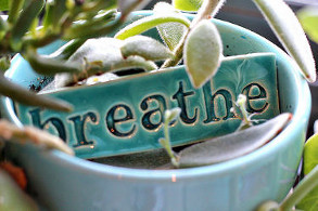 a ceramic tile with the word 'breathe' on it
